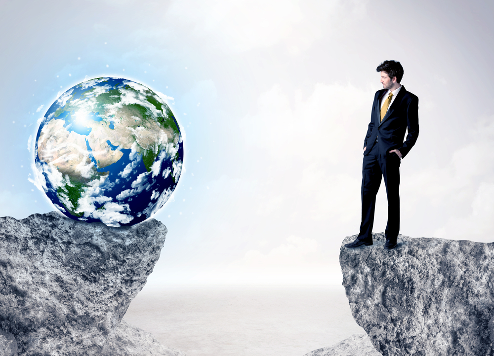 Businessman standing on the edge of mountain with a globe on the other side, Elements of this image furnished by NASA